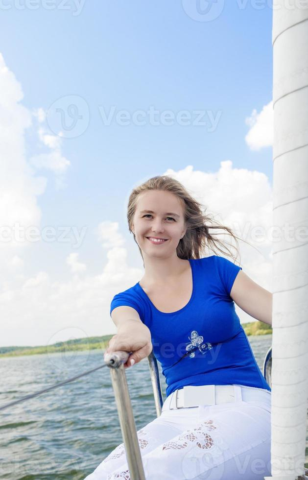Porträt der lächelnden kaukasischen Frau, die auf Yacht segelt foto