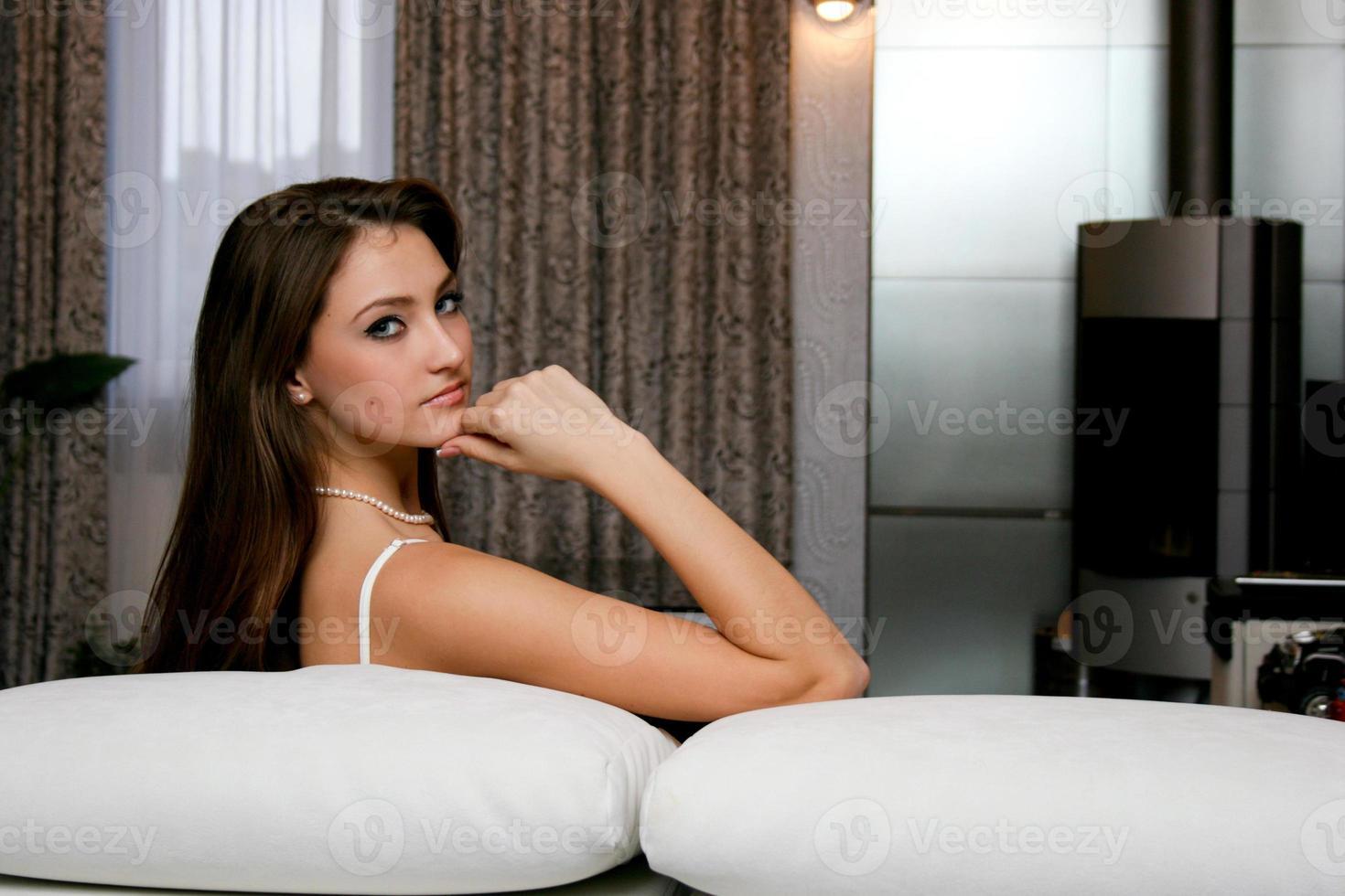 junge kaukasische ernste Frau, die auf dem Sofa sitzt foto