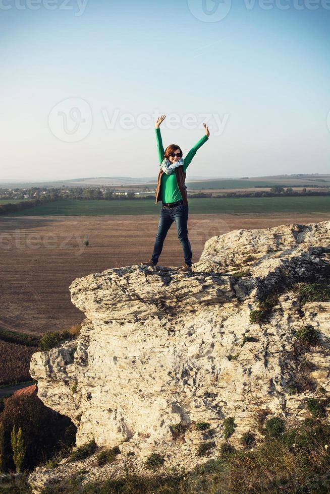 junge kaukasische positive Frau, die auf dem hohen Felsen aufwirft foto