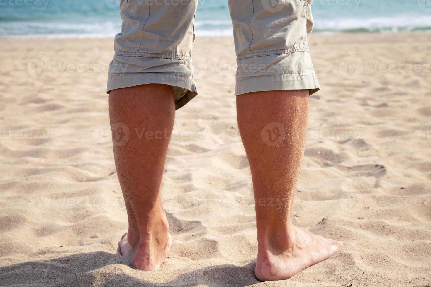 Beine des jungen kaukasischen Mannes, der auf Sandstrand steht foto