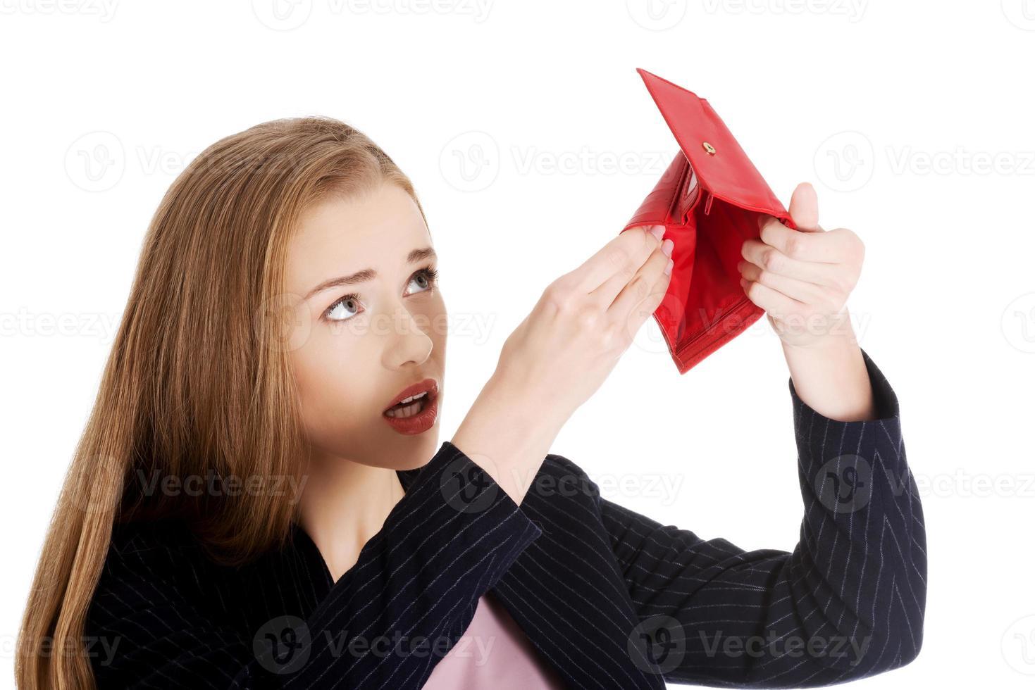 schöne kaukasische Geschäftsfrau, die ihre leere rote Brieftasche überprüft foto
