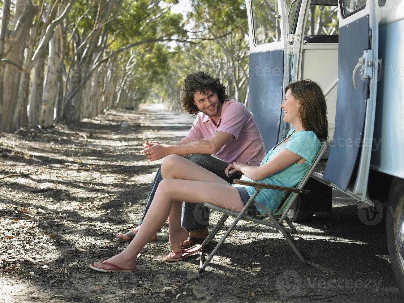 Paar sitzt auf Liegestühlen neben Wohnmobil foto