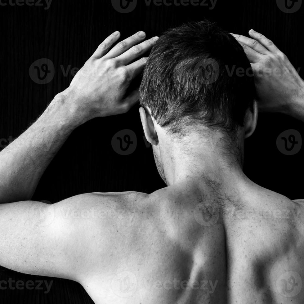 starker muskulöser junger kaukasischer Mann steht nahe schwarzer Wand foto