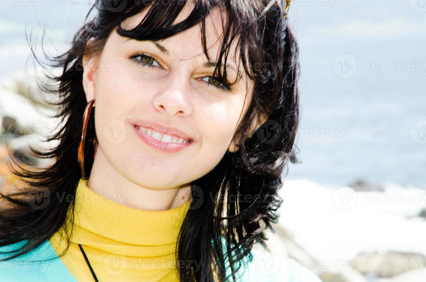 junge freudig lächelnde kaukasische Brünette am hellen sonnigen Strand foto