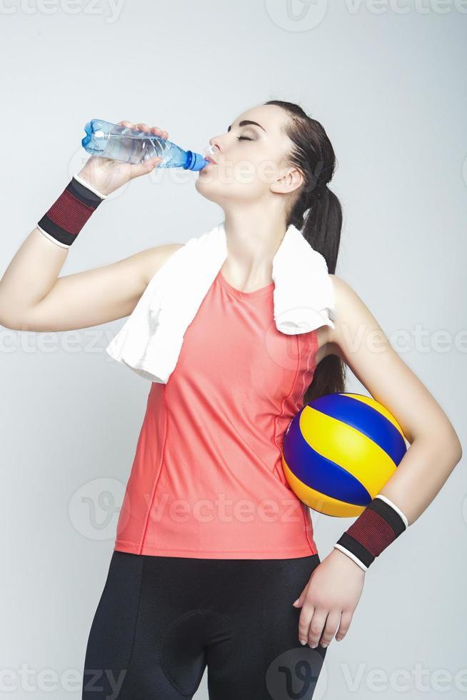 kaukasische weibliche professionelle Volleyballathletin, die Ball trinkt und hält foto