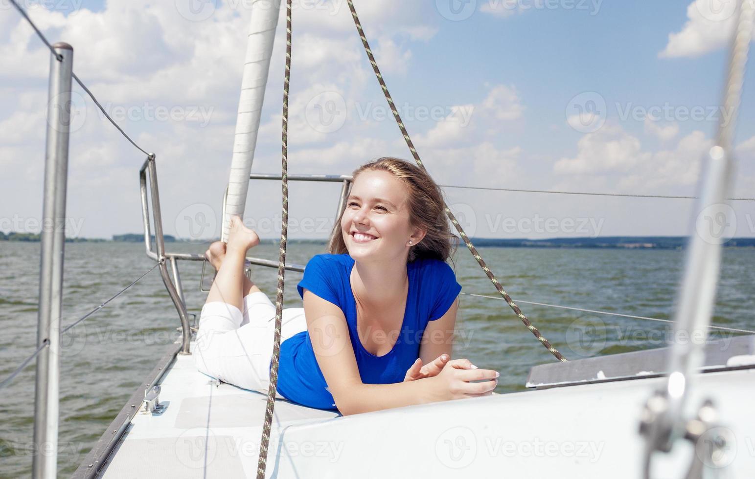 Reisekonzepte: lächelnde positive kaukasische Frau auf weißer Yacht foto