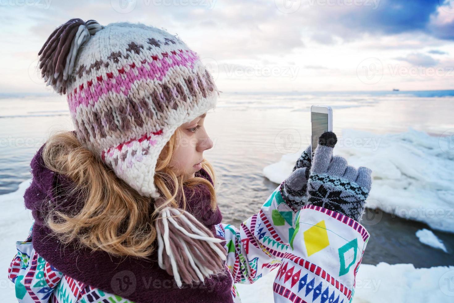 kleines blondes kaukasisches Mädchen, das Bilder auf ihrem Smartphone macht foto