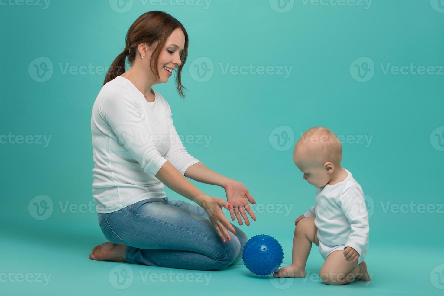 attraktive lächelnde junge kaukasische Mutter, die mit niedlichem Baby spielt foto