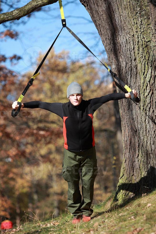 Outdoor-Suspensionstraining im Wald - kaukasischer Mann am Baum foto