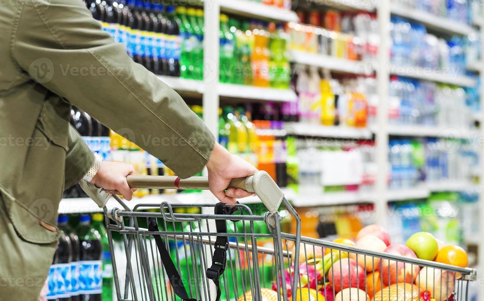 kaukasischer Mann, der einen vollen Wagen in einem Supermarkt schiebt foto