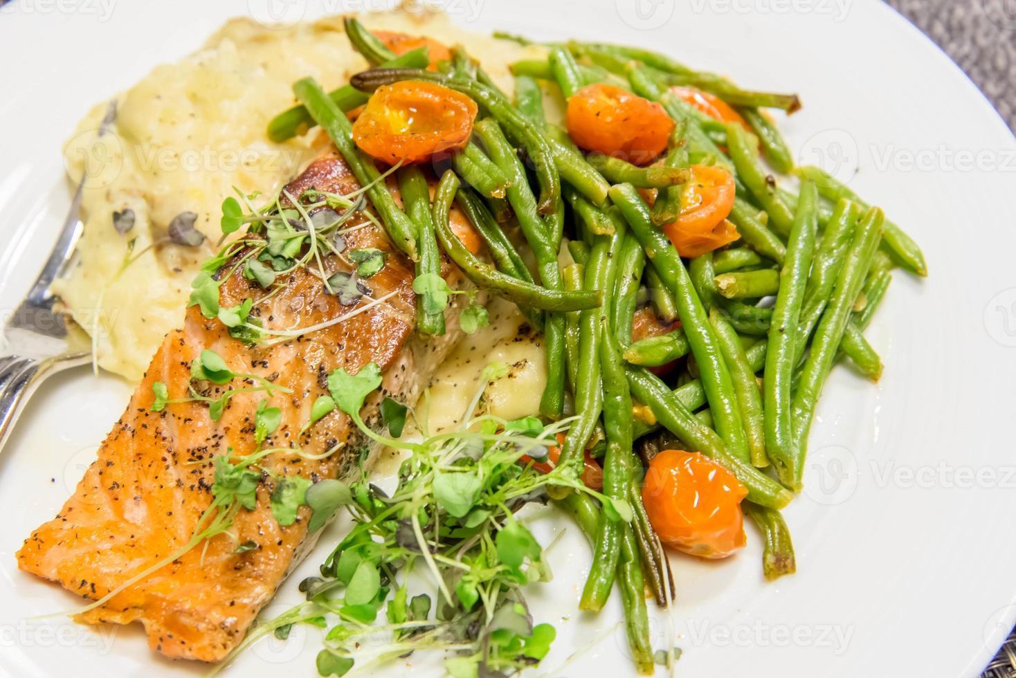 nahrhaftes Lachsessen mit grünen Bohnen und Tomaten foto