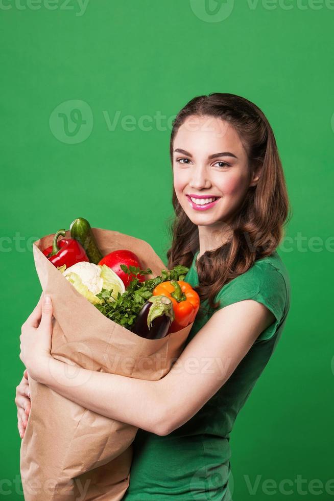 schöne glückliche Frau, die eine Einkaufstüte voll frisch hält foto