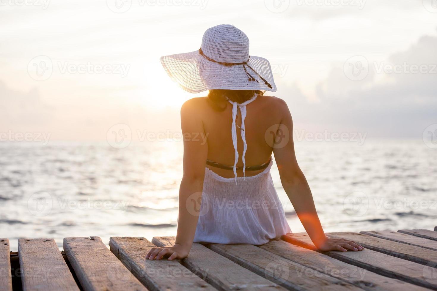 Die kaukasische Frau ruht sich am hölzernen Pier zum Indischen Ozean aus foto