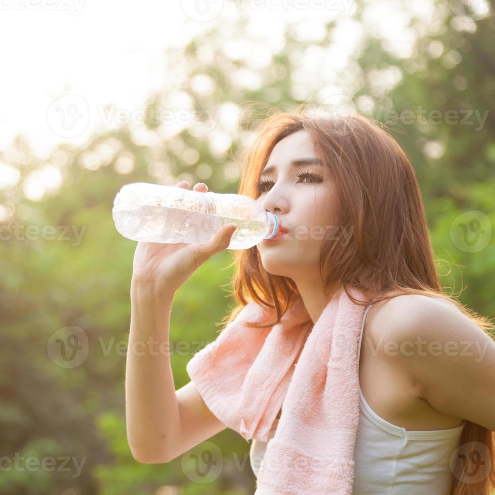 Frau sitzt müde und trinkt Wasser nach dem Training. foto