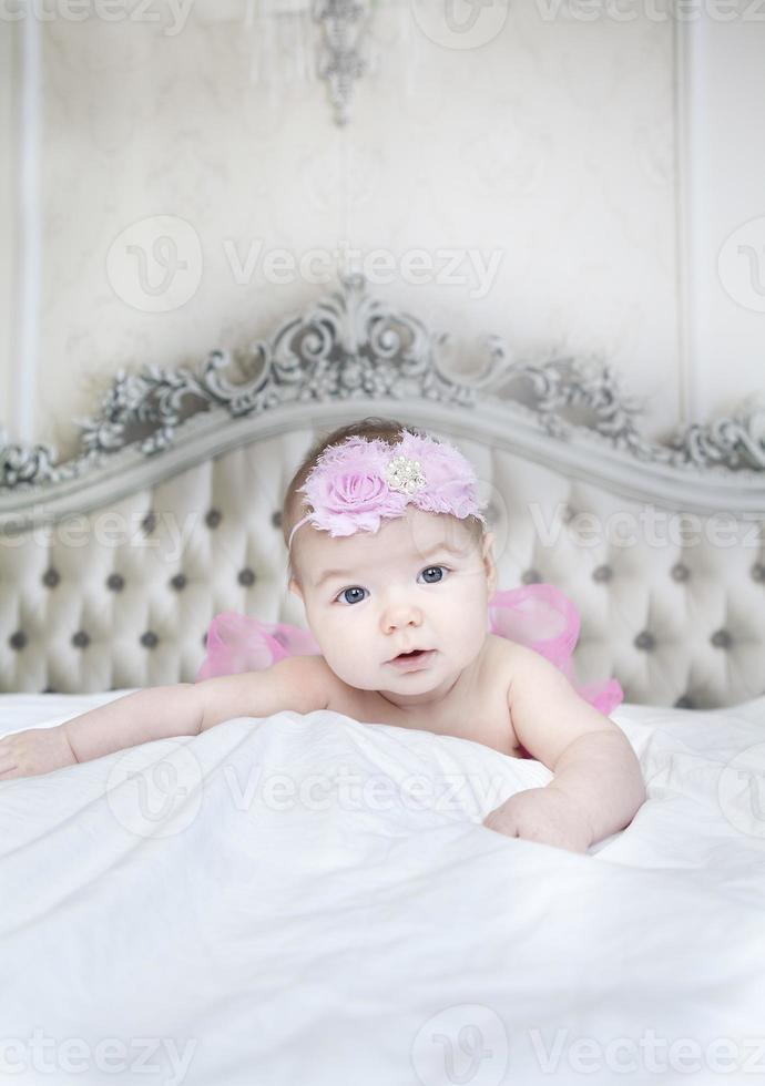 Baby Gril auf einem Bett mit einem antiken Kopfteil foto