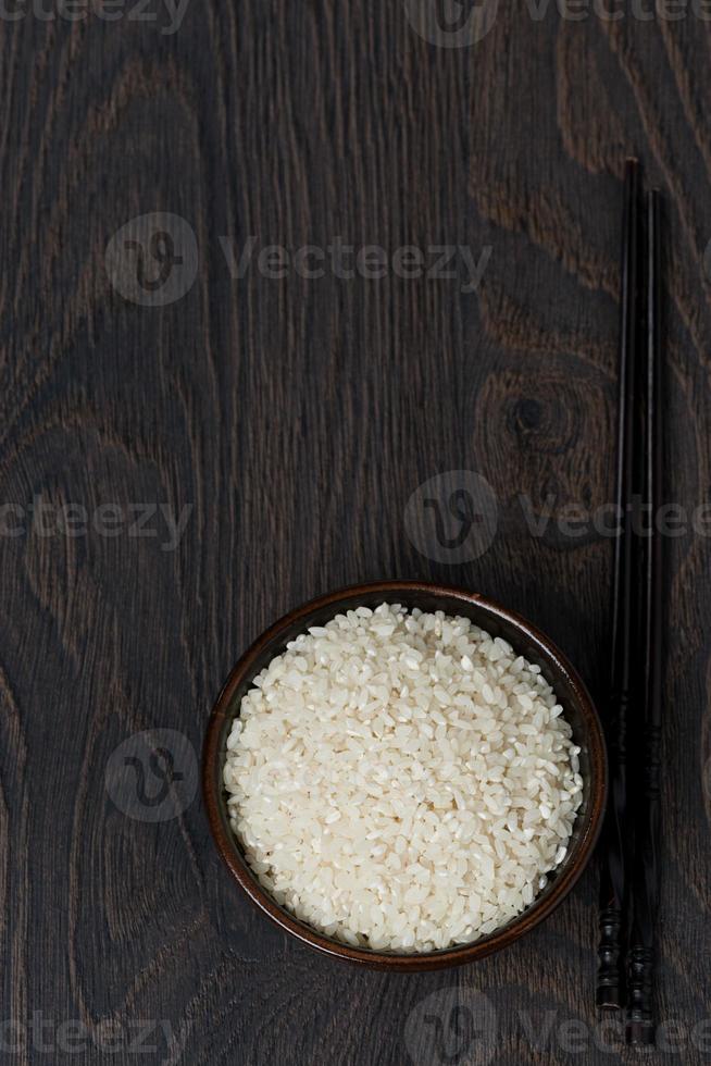 Reis in Schüssel und Essstäbchen auf dunklem Hintergrund, Draufsicht foto