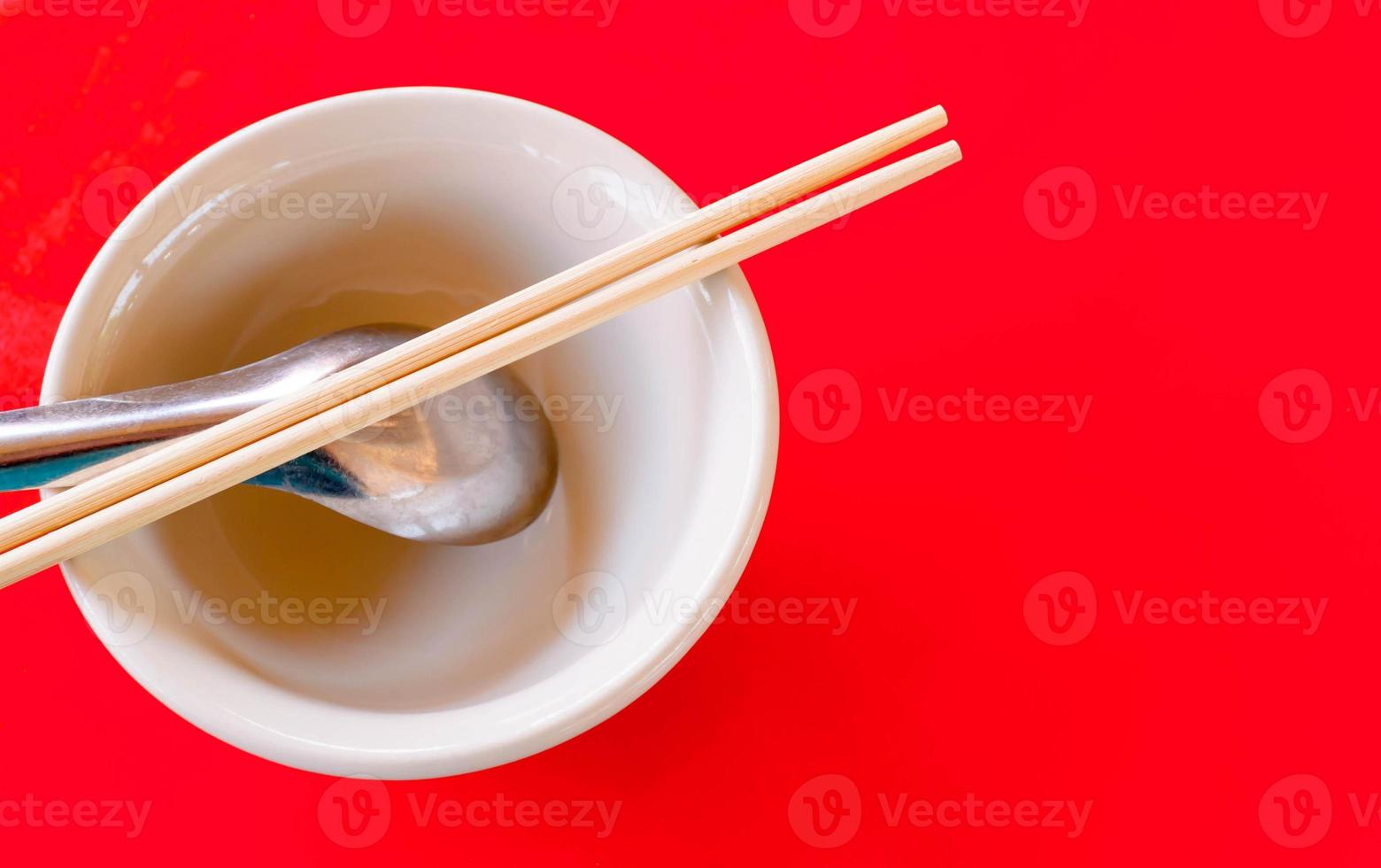 Reisschüssel und Löffel und Essstäbchen auf dem roten Tisch foto
