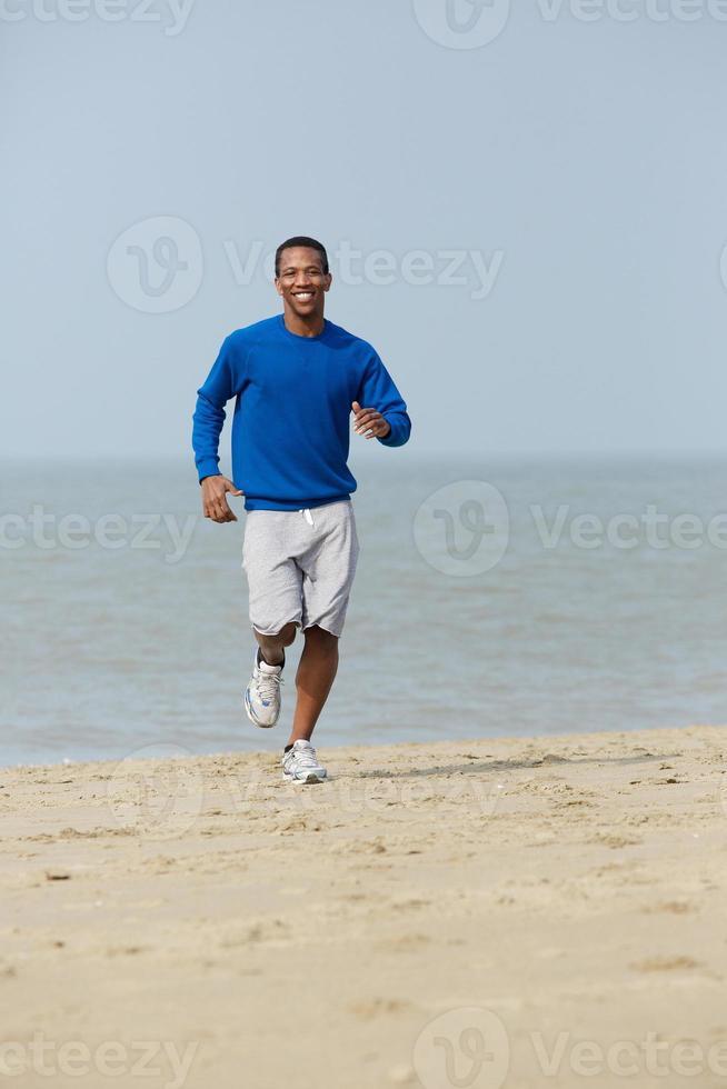 gesunder junger Mann, der am Strand joggt foto