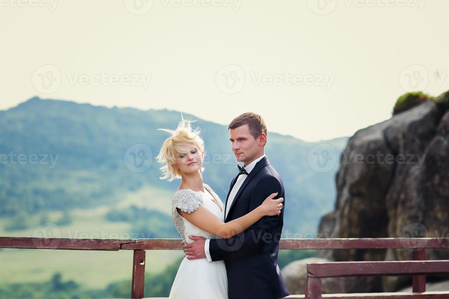 Hochzeitspaar posiert vor dem Hintergrund des Berges. Brid foto