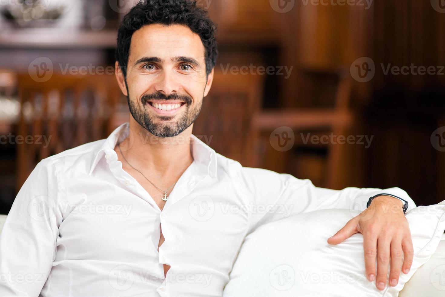 lächelnder junger Mann, der auf Sofa zu Hause entspannt foto