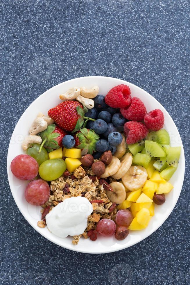 frische Lebensmittel für ein gesundes Frühstück - Beeren, Obst, Nüsse foto