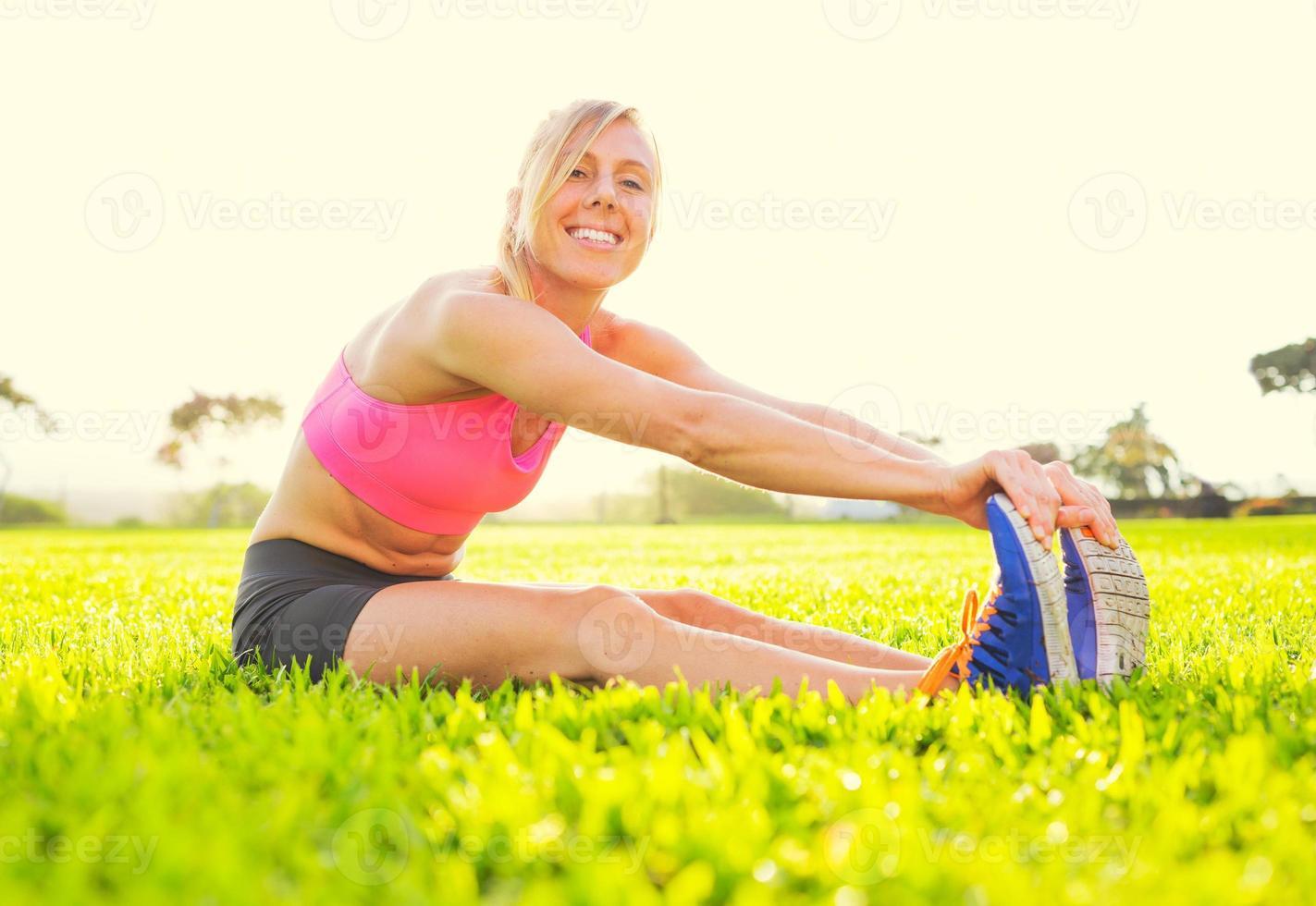 junge Frau, die sich vor dem Training streckt foto