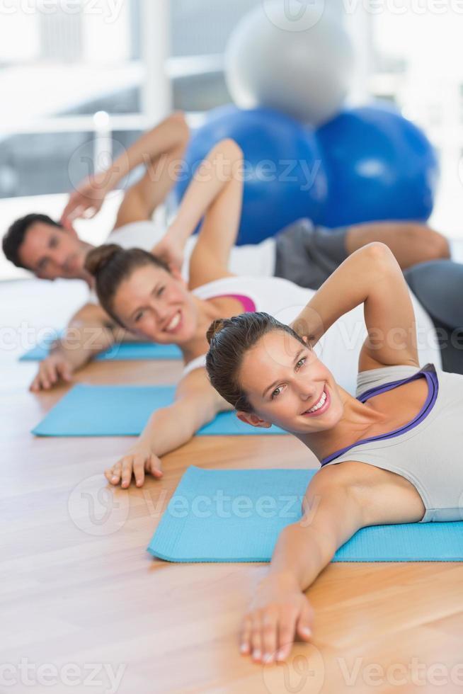 lächelnde Leute, die Pilateübungen im Fitnessstudio machen foto