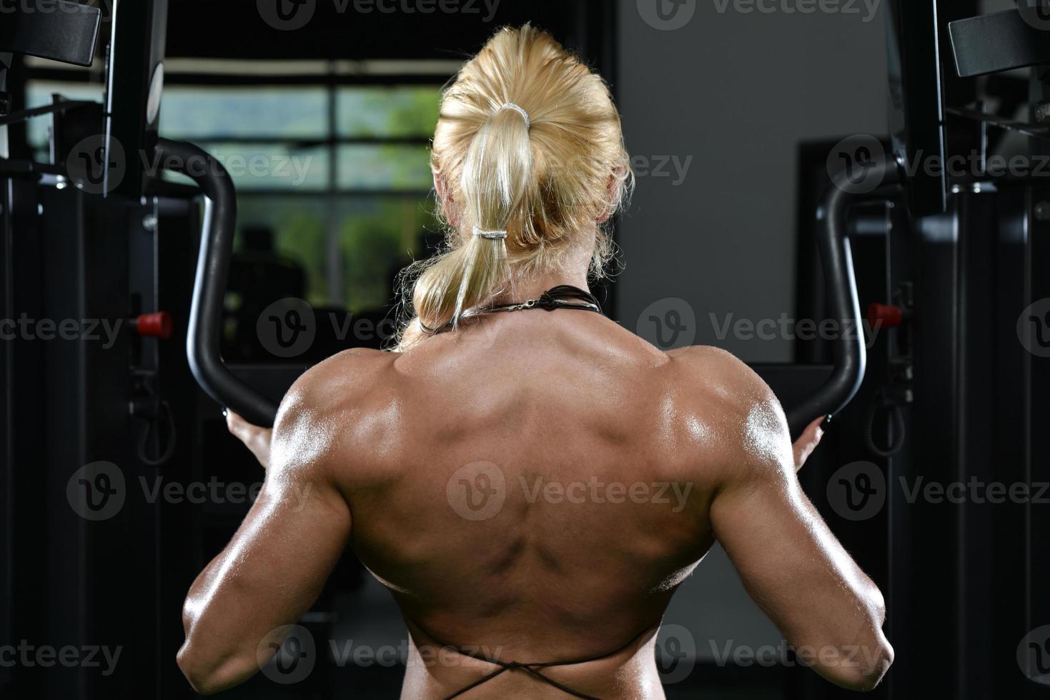junge Frau, die schweres Gewicht für Rücken macht foto