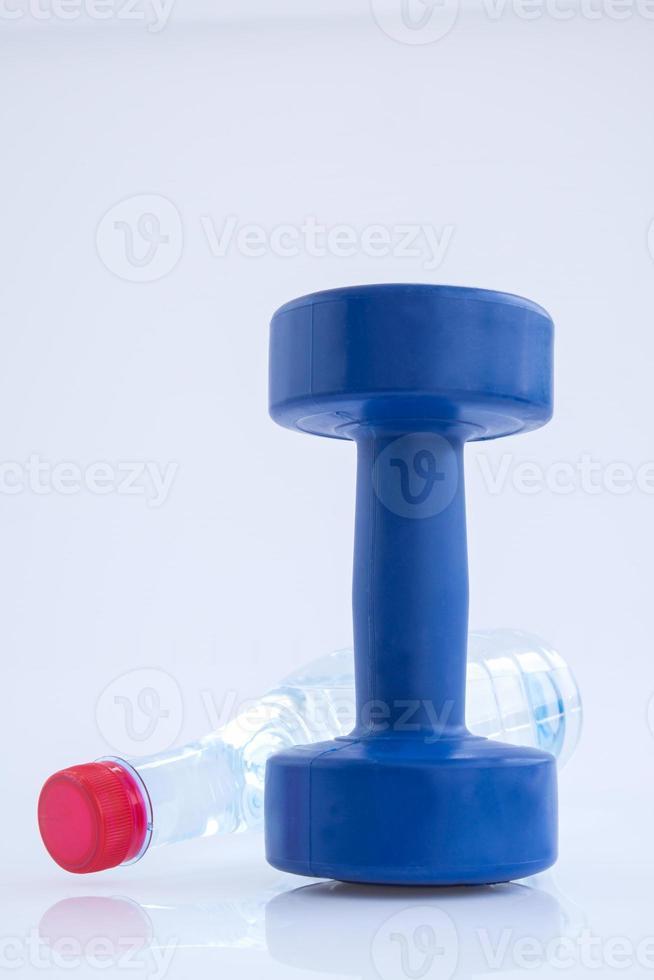 blaue kunststoffbeschichtete Hanteln und Wasserflasche isoliert auf weiß foto