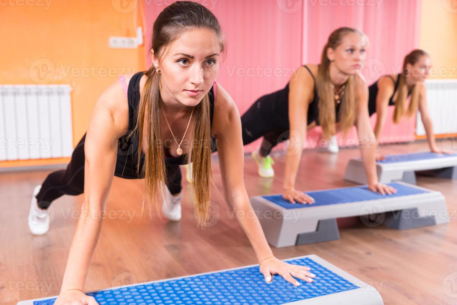 Gruppe von Frauen, die Plankenübungen in der Schrittklasse machen foto