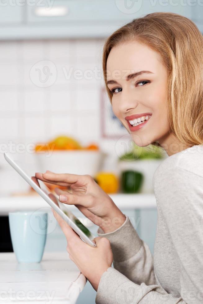schöne kaukasische Frau, die Tablette hält. foto