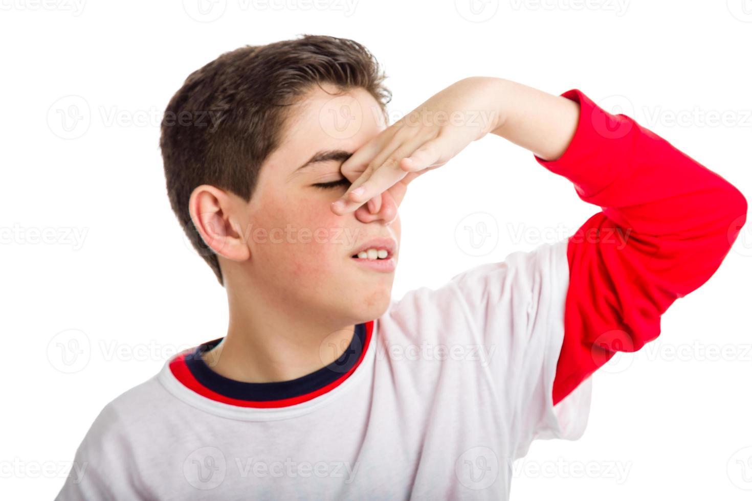 kaukasischer Junge, der seine Nase verstopft foto