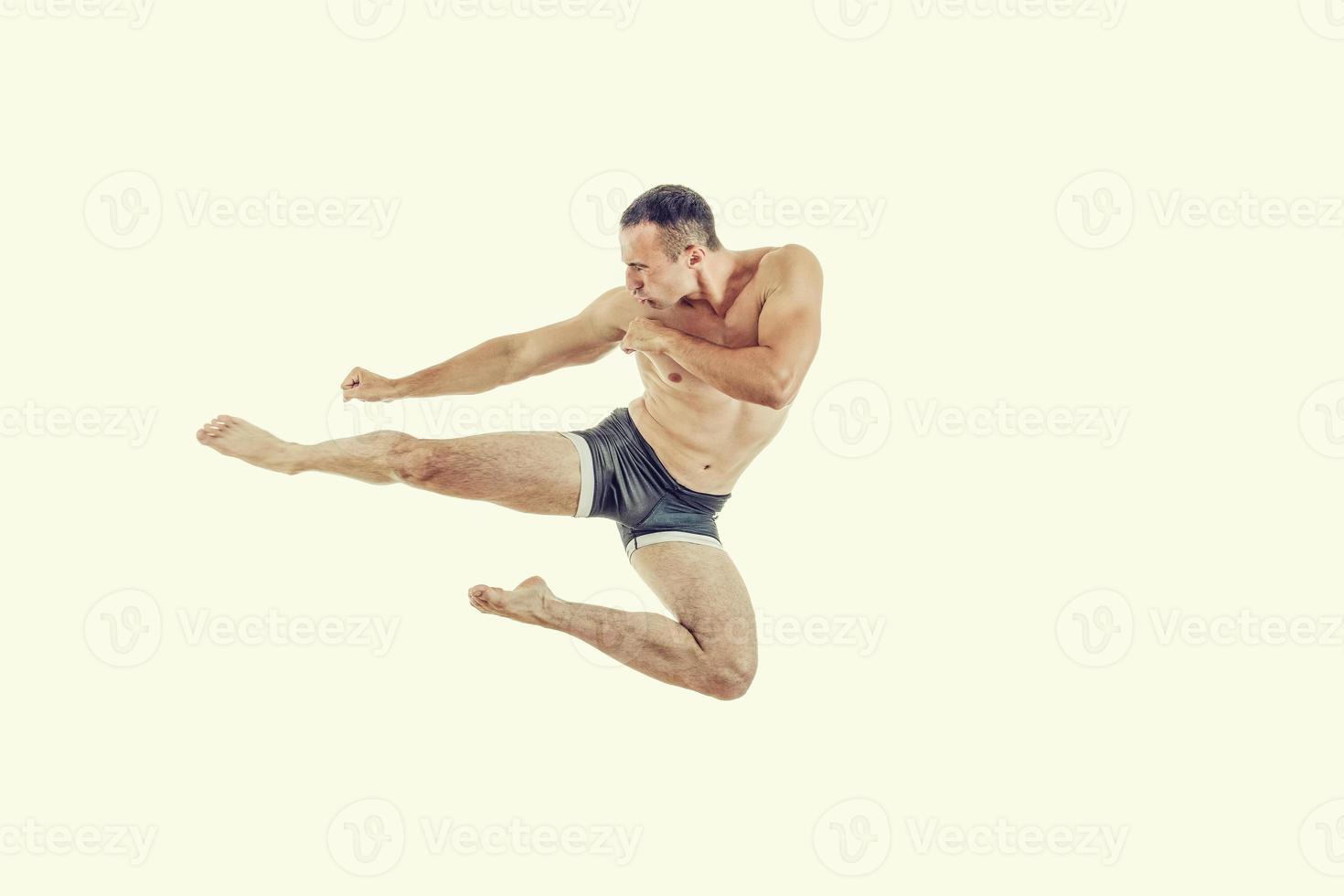 Ein kaukasischer Mann, der das Boxen beim Springen in die Luft ausübt, tritt foto