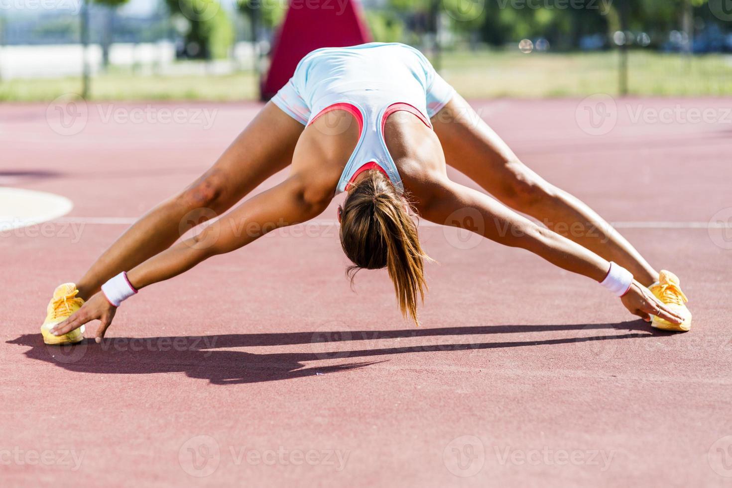 schöne junge sportliche Frau, die sich im Sommer ausdehnt foto