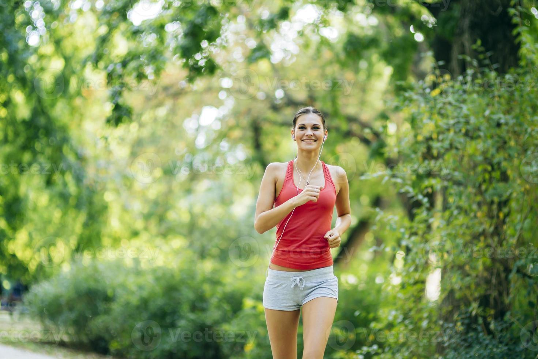 junger schöner Athlet, der im Park joggt foto