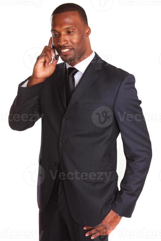 Afroamerikaner-Geschäftsmann, der auf Handy spricht foto