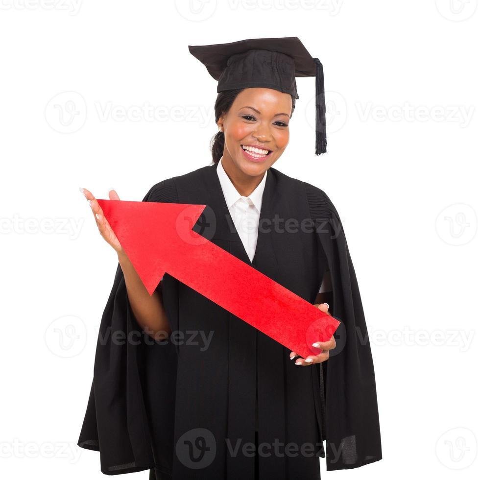 Afroamerikaner-Hochschulabsolvent, der roten Pfeil hält foto