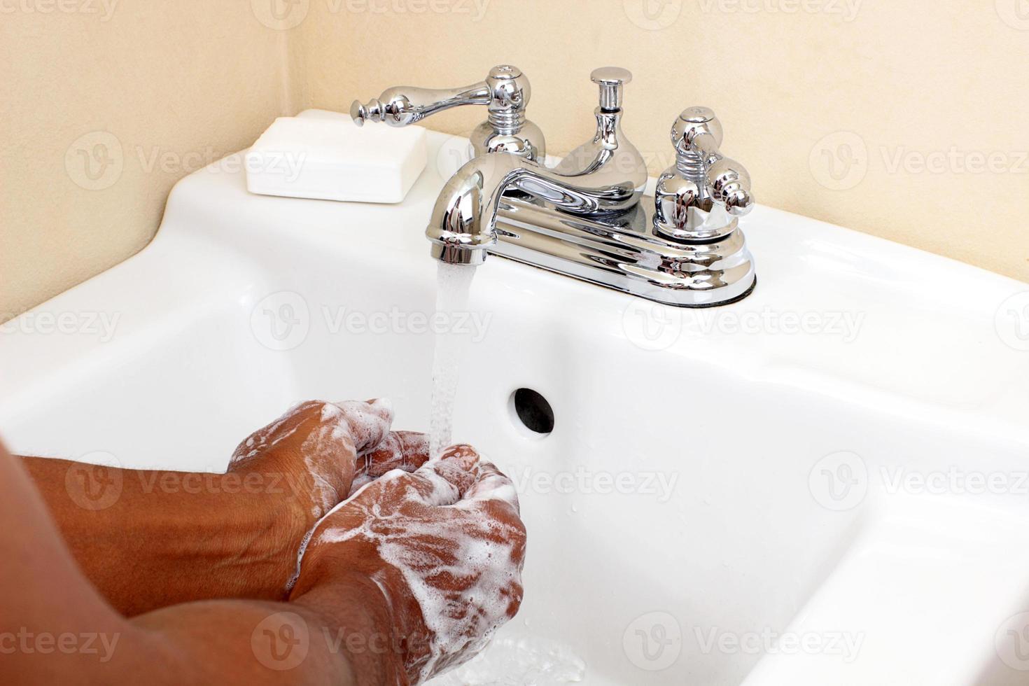 schwarze Person, die mit Wasser und Seife wäscht foto