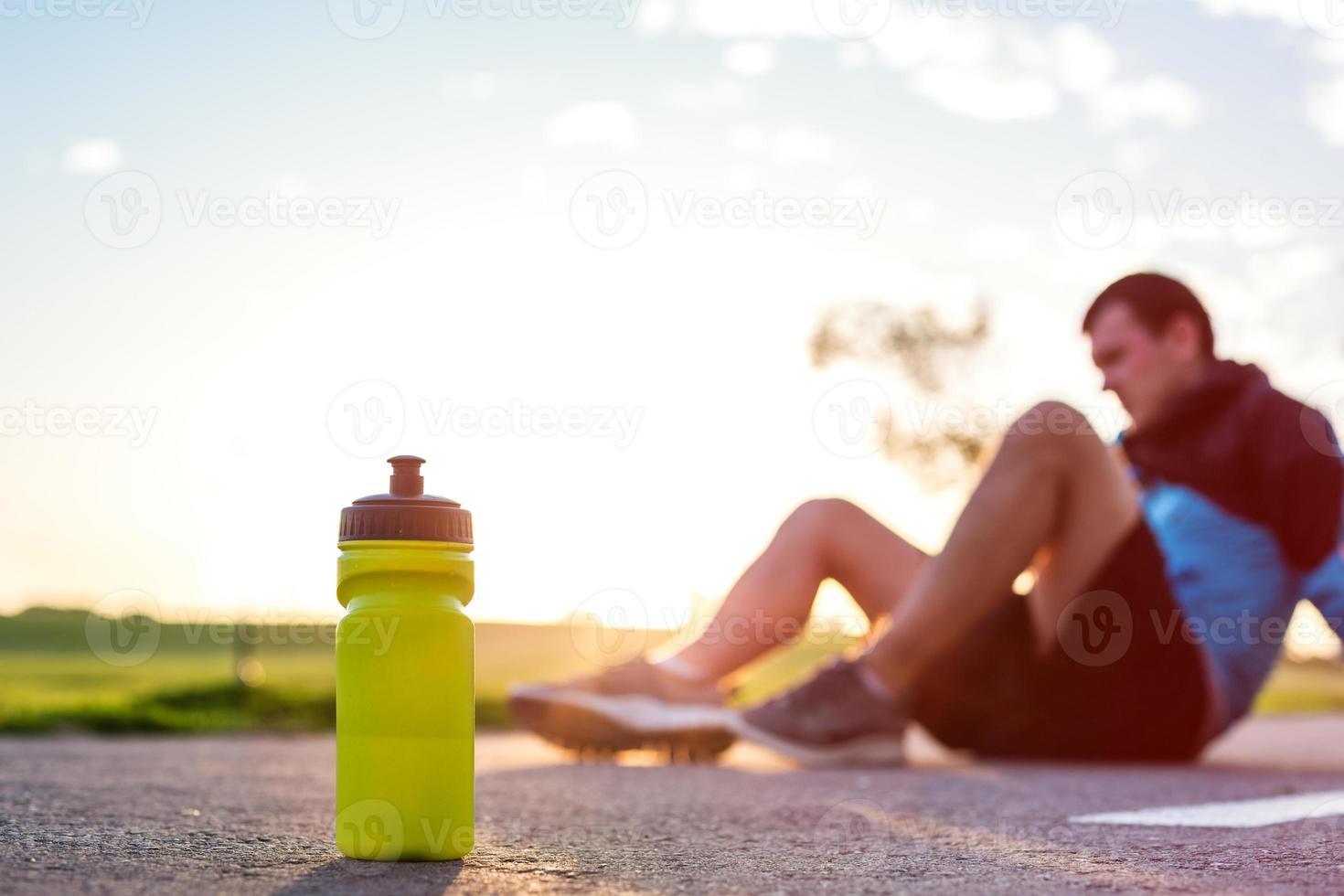 Sportflasche mit Wasser und Läufer foto