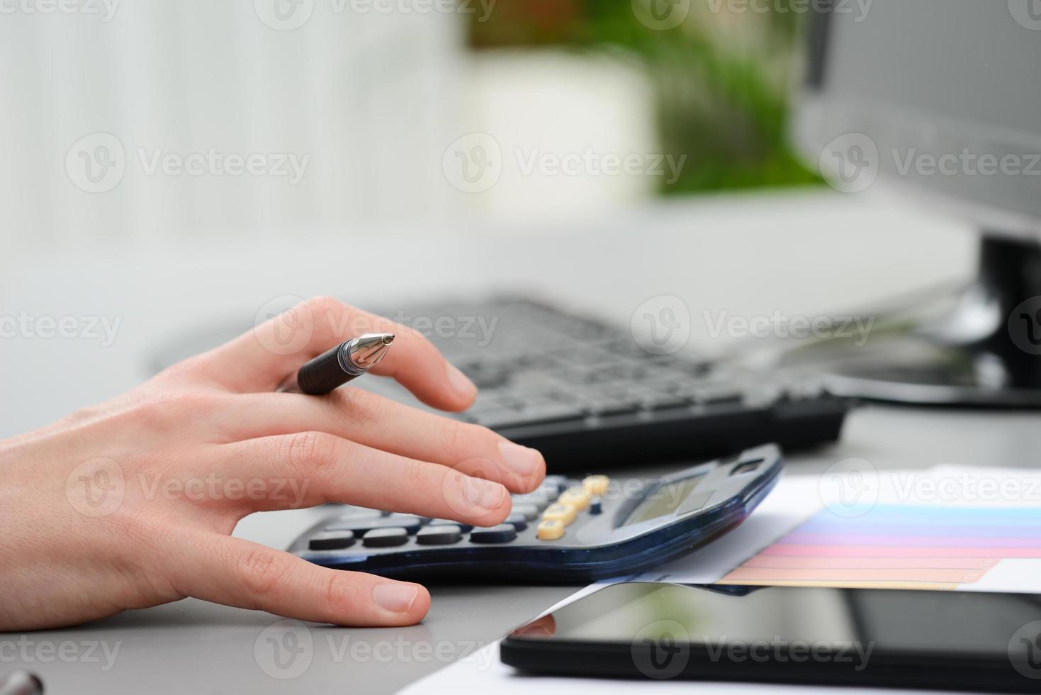 Detail der Hände, die auf Taschenrechner mit Desktop-Computertastatur tippen foto