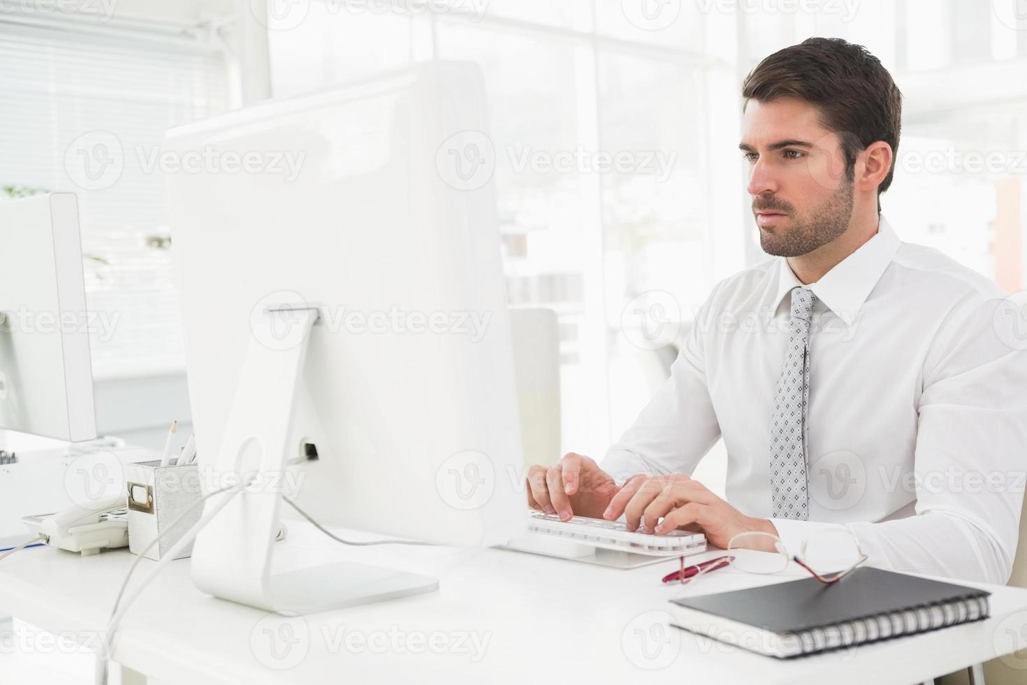 konzentrierter Geschäftsmann, der auf der Tastatur tippt foto