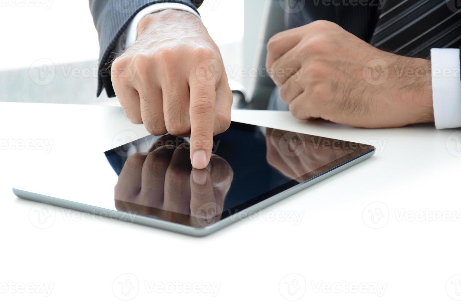 Geschäftsmannhand, die Tablet-Computer auf dem Tisch berührt foto