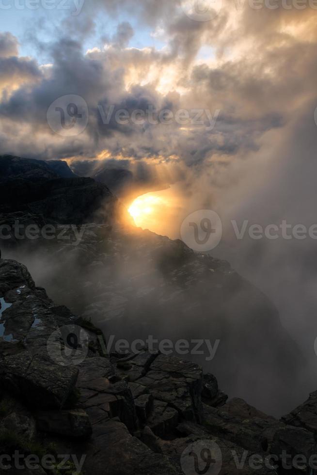 Sonnenstrahlen durch die Wolken, um einen Fjord zu beleuchten foto