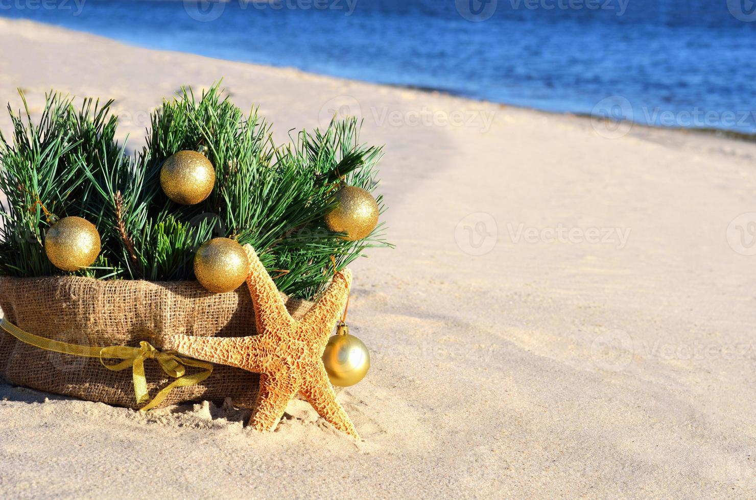 Weihnachtsbaum mit goldenen Weihnachtskugeln, Seestern auf Sand, Strand foto