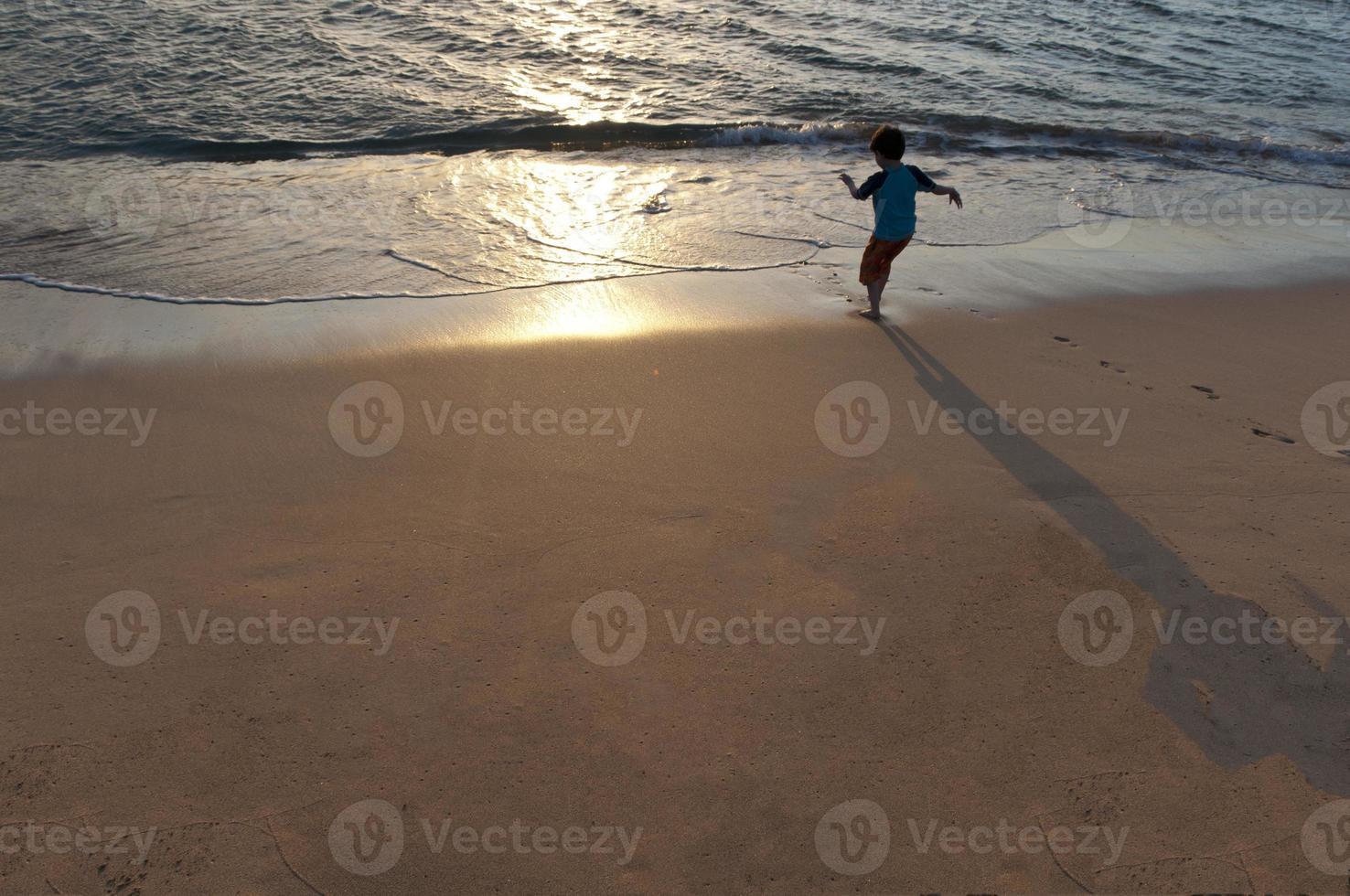 Junge läuft auf einem Hawaii-Strand. foto