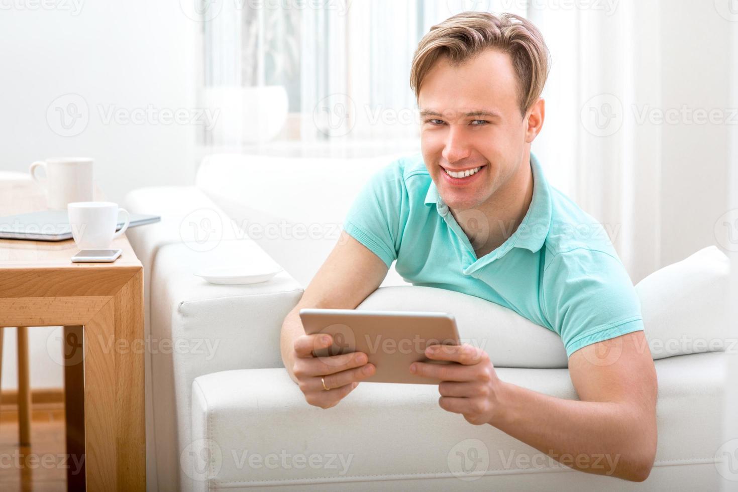 Mann mit Gerät zu Hause sitzen foto