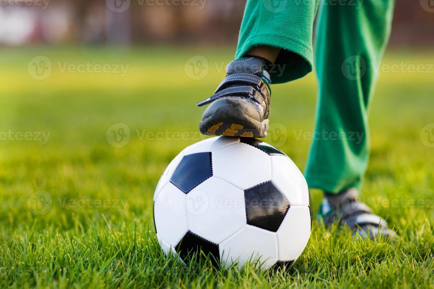 blonder Junge von 4, der Fußball mit Fußball nur Feld spielt foto