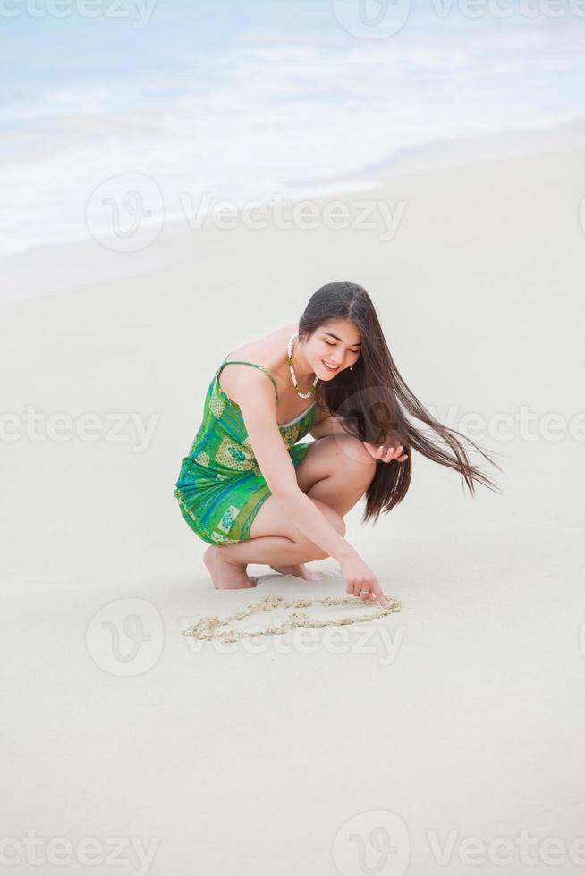 schönes jugendlich Mädchen, das Herz im Sand am tropischen Strand zeichnet foto