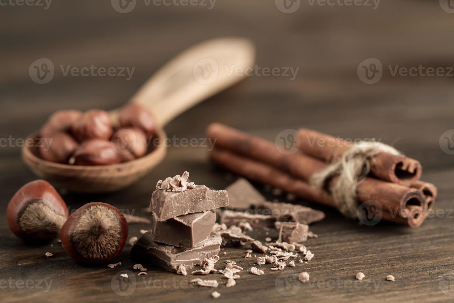 gebrochener Schokoriegel, Haselnuss und Zimt auf hölzernem Hintergrund, Nahaufnahme foto