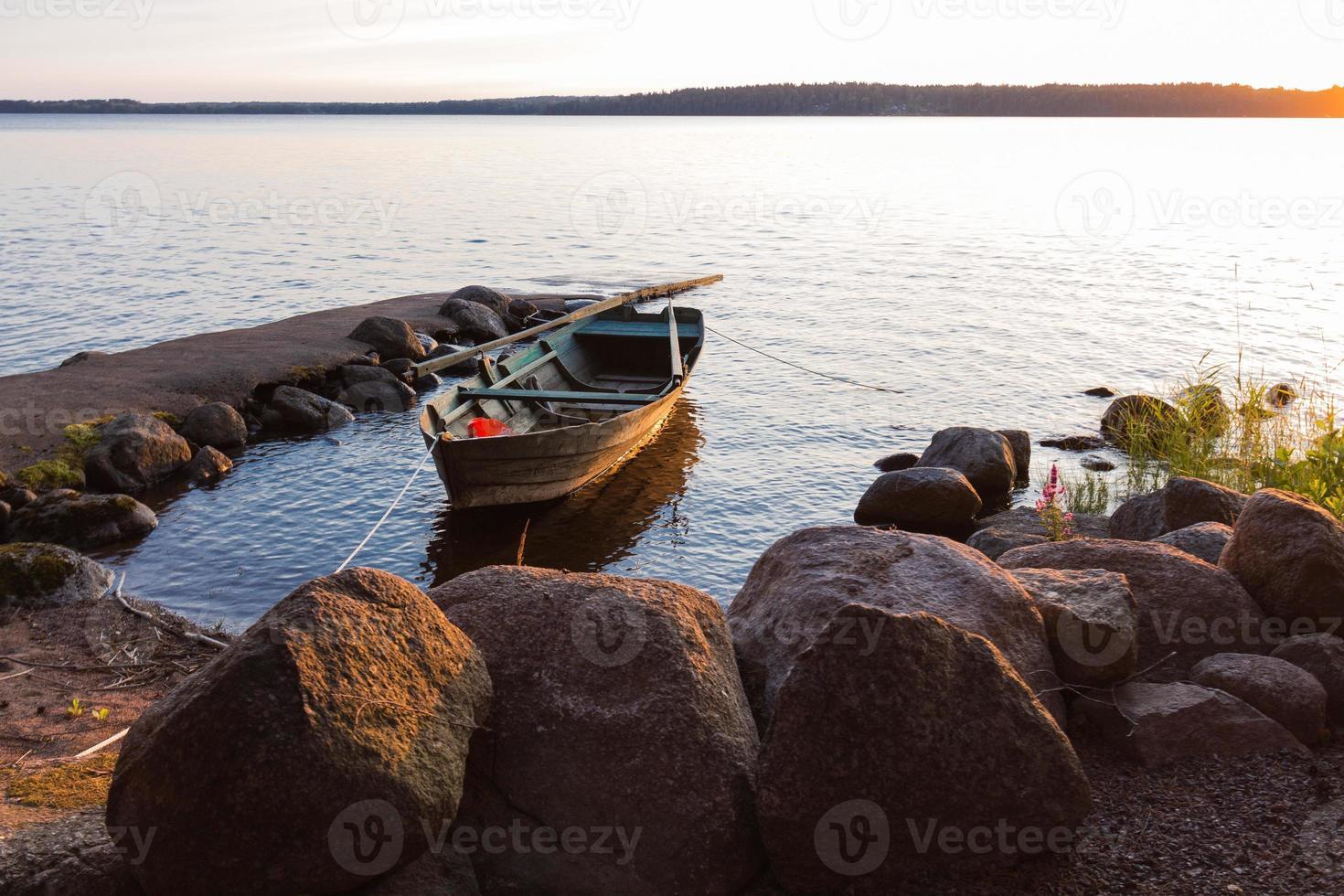 Das Boot wurde bei Sonnenuntergang an der Seite beleuchtet foto